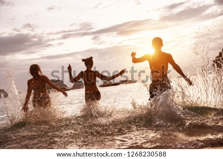 Group of happy friends run and jump at sunset sea beach. Tropical vacations concept #1268230588
