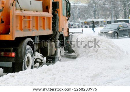 Night in the city the snow fell.His cleaning went snow-removal vehicles.They cleared the roads on the streets of the city. #1268233996