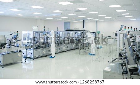 Shot Of Sterile High Precision Manufacturing Laboratory where Scientists in Protective Coverall's Use Computers and Microscopes, doing Pharmaceutics, Biotechnology and Semiconductor Research. #1268258767