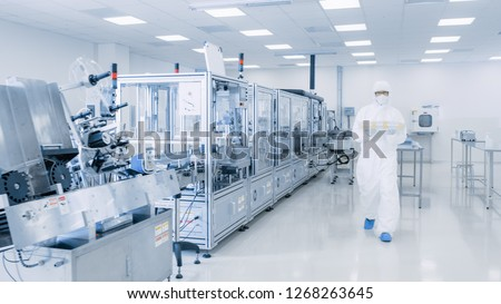Shot of Sterile Pharmaceutical Manufacturing Laboratory where Scientists in Protective Coverall's Do Research, Quality Control and Work on the Discovery of new Medicine. #1268263645