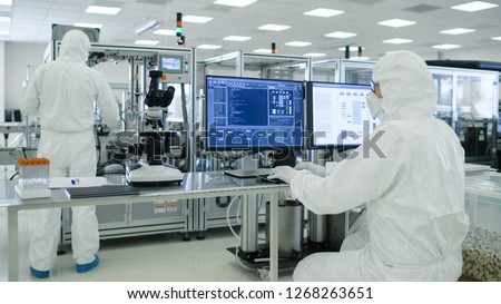 Shot of a Scientists in Sterile Suits Working with Computers, Analyzing Data form Modern Industrial Machinery in the Laboratory. Product Manufacturing Process: Pharmaceutics, Semiconductors #1268263651