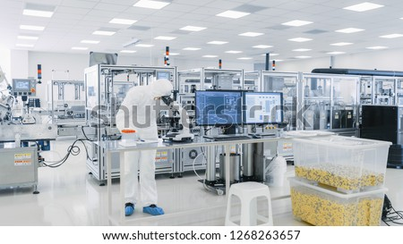Shot of Sterile Pharmaceutical Manufacturing Laboratory where Scientists in Protective Coverall's Do Research, Quality Control and Work on the Discovery of new Medicine. #1268263657