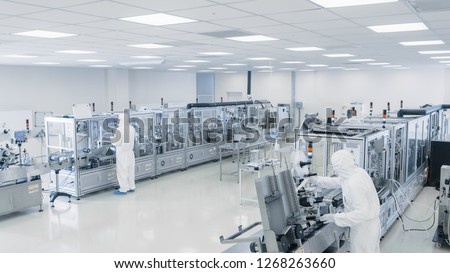 Sterile High Precision Manufacturing Laboratory where Scientists in Protective Coverall's Turn on Machninery, Use Computers and Microscopes, doing Pharmaceutics, Biotechnology Semiconductor Research. #1268263660