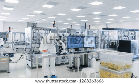 Shot of Sterile High Precision Manufacturing Laboratory where Scientists in Protective Coverall's Use Computers and Microscopes, doing Pharmaceutics, Biotechnology and Semiconductor Research. #1268263666