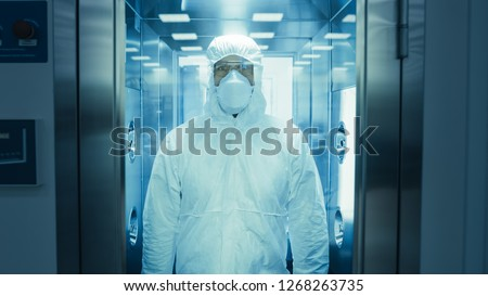 Scientist / Virologist / Factory Worker in Coverall Suit Disinfects Himself in Decontamination Shower Chamber. Biohazard Emergency Response. Royalty-Free Stock Photo #1268263735