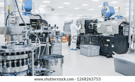 On a Factory Scientist in Sterile Protective Clothing Work on a Modern Industrial 3D Printing Machinery. Pharmaceutical, Biotechnological and Semiconductor Manufacturing Process Shot from Inside. #1268263753