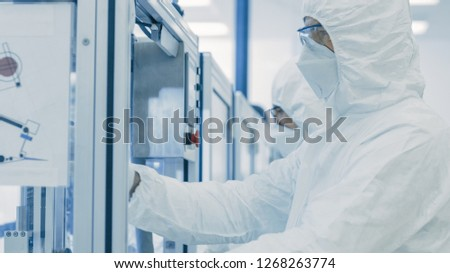 In the Manufacturing Facility Team of Scientist Wearing Sterile Protective Coverall Set's up / Programs Modern Industrial 3D Printer, High Precision Manufacture of Semiconductors under Process. #1268263774