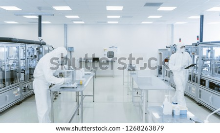 Quality Control Check: Scientist Using Digital Tablet Computer and wearing Protective Suit walks through Manufacturing Laboratory. Product Manufacturing: Pharmaceutics, Semiconductors, Biotechnology. #1268263879