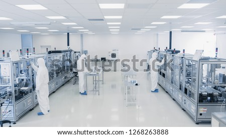 Shot Of Sterile Pharmaceutical Manufacturing Laboratory where Scientists in Protective Coverall's Do Research, Quality Control and Work on the Discovery of new Medicine. #1268263888