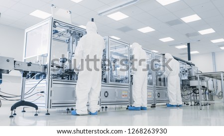 In the Manufacturing Facility Team of Scientist Wearing Sterile Protective Coverall Set's up / Programs Modern Industrial 3D Printer, High Precision Manufacture of Semiconductors under Process. #1268263930