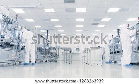 Team of Research Scientists in Sterile Suits Working with Computers, Microscopes and Industrial Machinery in the Laboratory. Product Manufacturing Process: Pharmaceutics, Semiconductors, Biotechnology #1268263939