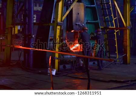 Blacksmith processes the iron product under a huge press, forging metal, stamping. Hot metal ingot being loaded in a hammer forge. Worker forges iron products. Metallurgical, forge plant #1268311951
