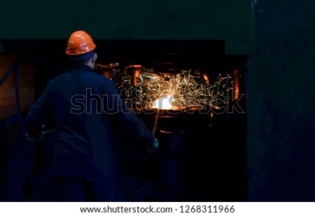 Blacksmith processes the iron product under a huge press, forging metal, stamping. Hot metal ingot being loaded in a hammer forge. Worker forges iron products. Metallurgical, forge plant #1268311966