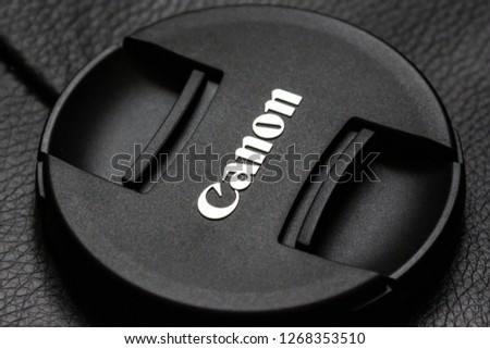 COPENHAGEN, DENMARK - MARCH, 10, 2018: Canon lens cap with the logo at an angle on leather pattern background  #1268353510