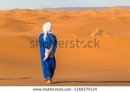 View from behind to Berber in traditional clothing. Erg Chebbi desert, Morocco Royalty-Free Stock Photo #1268370124