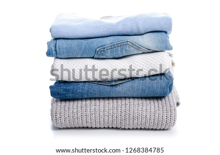 Stack of clothing jeans sweaters on a white background isolation #1268384785