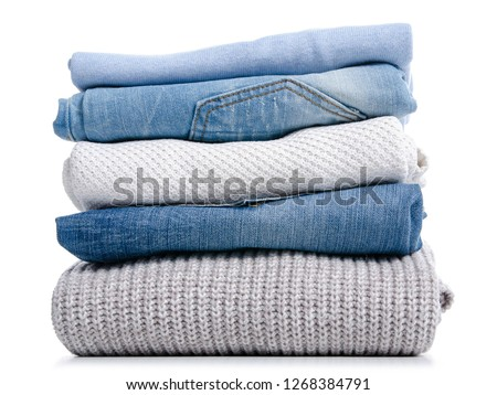 Stack of clothing jeans sweaters on a white background isolation #1268384791