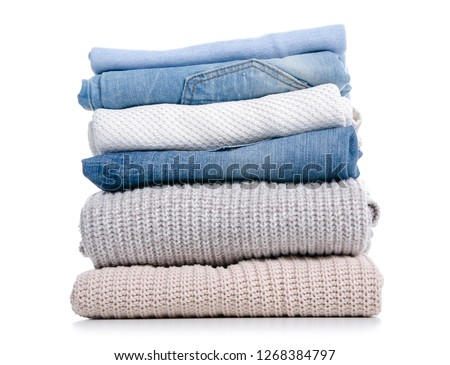 Stack of clothing jeans sweaters on a white background isolation #1268384797