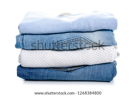 Stack of clothing jeans sweaters on a white background isolation #1268384800