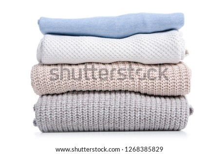 Stack folded sweaters on white background isolation #1268385829