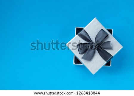 background for Valentine's day holiday, gift for Valentine's day, heart and gift box on blue background