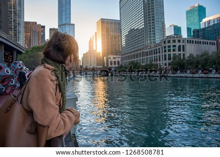 Asian women stand in the City of Chicago downtown and Chicago River with bridges during sunset.  #1268508781