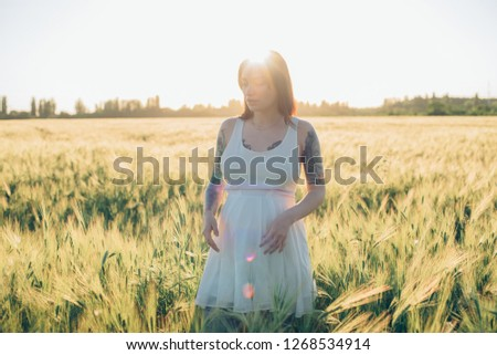 young pregnant tattooed female having fun in field during sunset #1268534914