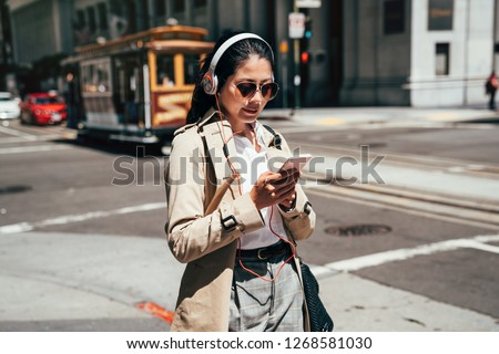 fashion college girl listening music with headphones and smart phone online walking on street in san francisco with cable car driving through. student in sunglasses using cellphone streetcar in back. #1268581030