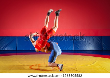 The concept of fair wrestling. Two greco-roman  wrestlers in red and blue uniform wrestling   on a yellow wrestling carpet in the gym #1268605582