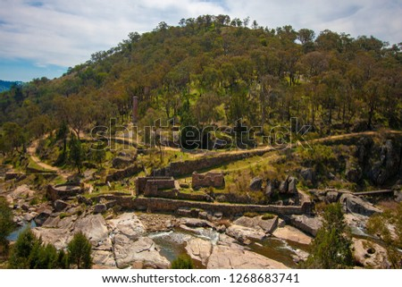 Narrow small mountain river at the foot of a round green hill. At the foot of the hill are the ruins of a gold factory. Australia. #1268683741