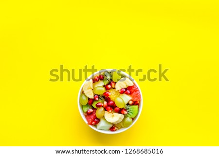 Light healthy breakfast or appetizer. Fruit salad with apple, kiwi and pomegranate in bowl on yellow background top view space for text #1268685016