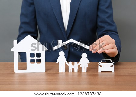 Woman with cutout paper family, house and car at table, closeup. Life insurance concept #1268737636