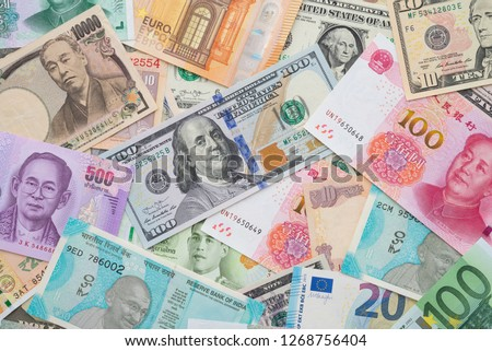 Flat lay or top view of world international banknotes vary countries background. US Dollar, Chinese yuan, Japanese yen, Euro, Indian rupee, Thai baht. Concept of Forex or global financial economic. Royalty-Free Stock Photo #1268756404