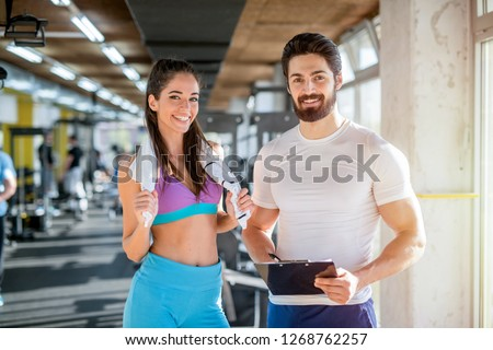 Picture of personal fitness trainer and his female client in gym posing in front of the camera. Royalty-Free Stock Photo #1268762257