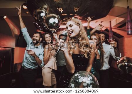 Singing Songs. Black Dress. Have Fun. Celebration. Background. Trendy Nightclub. Cheerful. Smiling Girl. Singing Songs. Handsome Men. Beautiful Girls. Friends at Karaoke Club. Karaoke Club. #1268884069