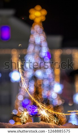 Christmas tree light night blur bokeh holiday abstract background Sparkler in the foreground #1268885575