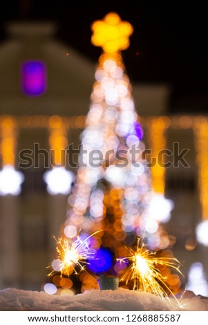 Christmas tree light night blur bokeh holiday abstract background Sparkler in the foreground #1268885587