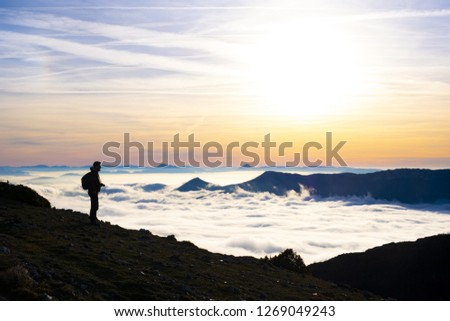 ARALAR, SPAIN - December 23, 2018: Man walking among mountains with a sea of clouds and the morning sun #1269049243