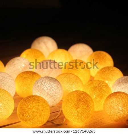 Yellow cotton light balls shining in the dark on the wooden floor. New Year lamps. Cotton Christmas garland. Creative backlight. #1269140263