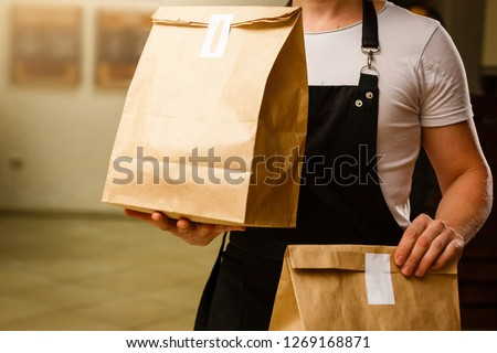 Two boxes with fast food being carried by delivery man in uniform for one of clients #1269168871