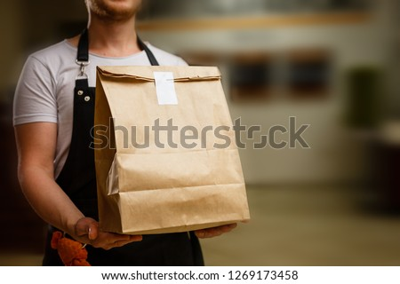 Diverse of paper containers for takeaway food. Delivery man is carrying #1269173458