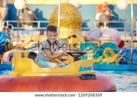 Cute European boy in striped t-shirt is driving water boat in the Luna park. He is enjoying his holidays and smiling to the camera. #1269268369