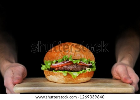 man hold burger on wooden plank. burger isolated on black. waiter hold tray #1269339640