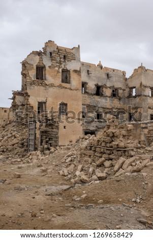 Crumbling ruins of old buildings in the coastal town of Mirbat, near Salalah, Dhofar Province, Oman #1269658429