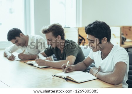 International company employees taking refresh training. Multiethnic group of three students writing notes during class. Career course concept #1269805885