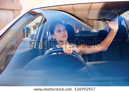 successful businesswoman driving car through modern urban city with reflections of buildings #126992957