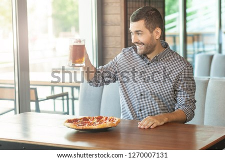 man holding up glass of beer and looking in the window of cafe #1270007131