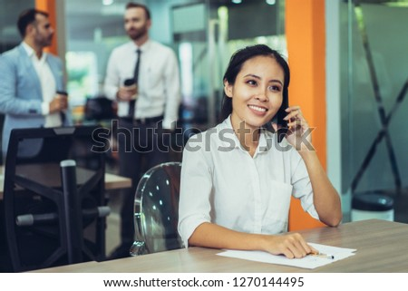 Smiling young Asian business woman talking on phone and working at desk in office. Two coworkers relaxing and standing in background. Management and communication concept. #1270144495