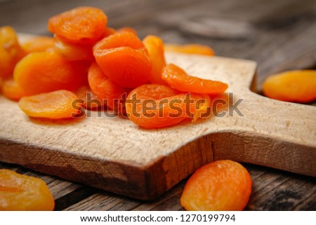 Dried apricots and kitchen cutting board on a old wooden table #1270199794