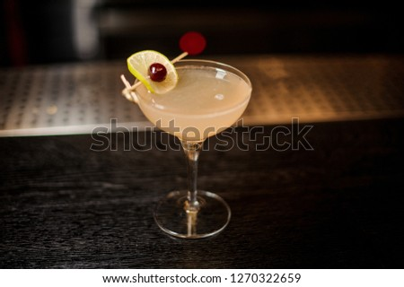 Elegant cocktail glass filled with fresh juicy sweet cocktail decorated with orange od cherry on the bar #1270322659